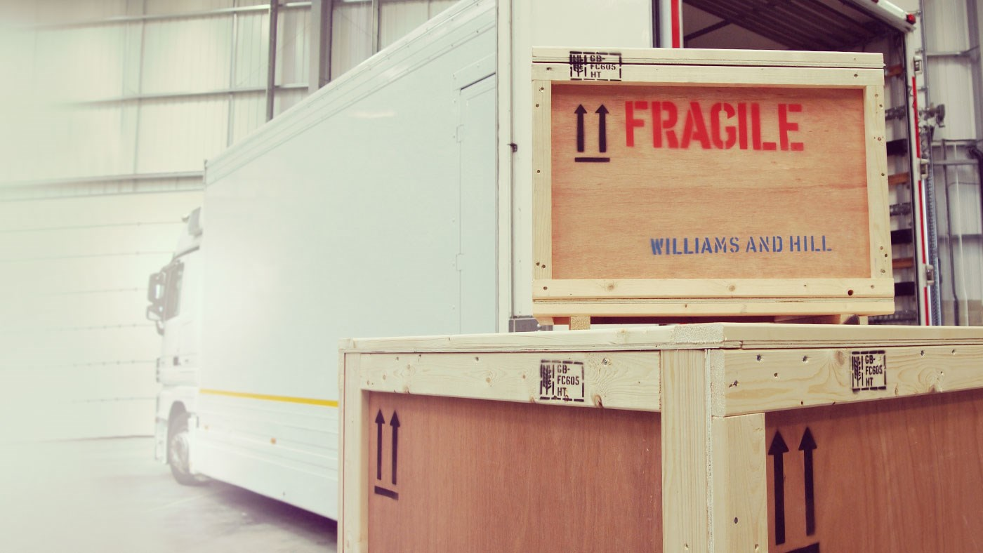 Two crates sit stacked beside a large Williams and Hill lorry waiting to be transported.