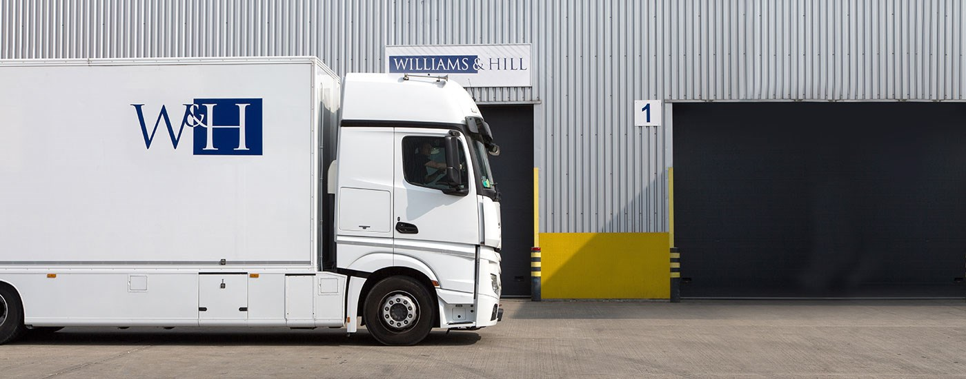 A white Williams and Hill lorry is parked outside the warehouse.