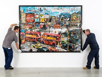 Two Williams and Hill employees hang a large piece of fine art.