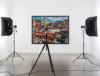 A large piece of fine art hangs in a studio surrounded by lighting equipment.