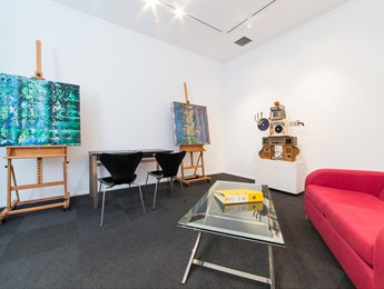 A cosy space with coffee table, sofa, desk and easels for displaying your art.