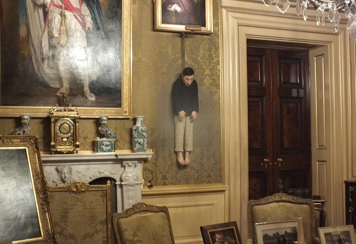 "An image showing the Cattelan sculpture ""Untitled"" hanging from chains in the Green Drawing room at Blenheim Palace"